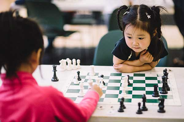 Two young girls playing chess with ivona Jezierska