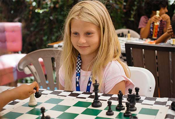 Girls smiling and playing Chess with ivona Jezierska organized Chess tournament.